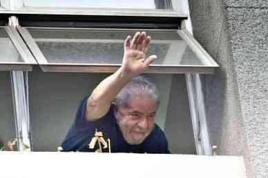 Former Brazilian President Luiz Inacio Lula da Silva waves at supporters from a window of the Workers Party (PT) state headquarters in Sao Paulo, Brazil, on March 4, 2016.   Police searched the home of Brazil's powerful ex-president Luiz Inacio Lula da Silva and detained him for questioning Friday in a probe into a huge corruption scheme. The detention of Lula da Silva for questioning and the search of his home by officers probing a corruption network amounts to an attack on the rule of law, his spokesman said Friday. AFP PHOTO / NELSON ALMEIDA